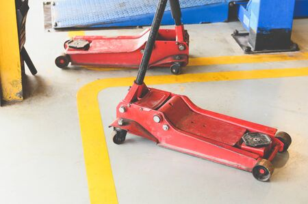 Hydraulic jack for lifting up car and vehicle in repairing garage workshop service center. Tool and equipment of automotive concept. Banco de Imagens