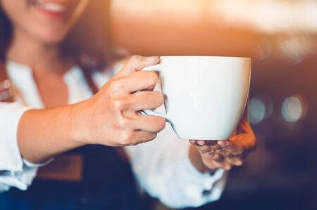 Closeup of professional female barista hand making and holding white cup of coffee. Happy young woman at counter bar in restaurant background. People lifestyles and Business occupation concept Stock Photo
