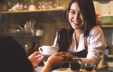Beautiful Asian female barista serving hot coffee to customer at counter bar background. Smiling woman and occupation. Stock Photo