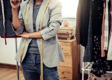 Closeup of lower body of fashion stylist designer in business owner workshop. Tailor and sewing concept. Portrait of happy casual trendy fashion designer businesswoman in studio. Job and occupation Stock Photo