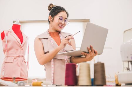 Happy Asian female fashion designer working in clothing shop studio and using laptop computer to contact customer. Woman creating design new collection . Tailor sewing. People lifestyle concept