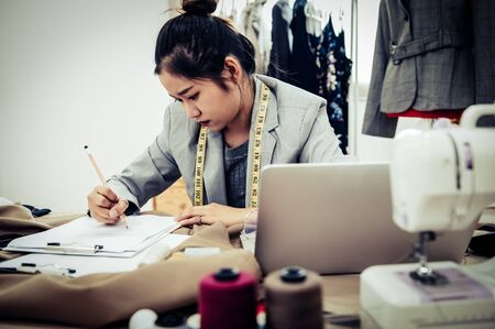Business Asian fashion designer have no idea when designing new collection of dress in workshop studio. Dressmaker headache and negative thinking concept. Tailor woman stressed writing zigzag stroke