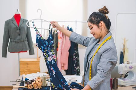 Asian female fashion designer girl making designing new beautiful blue dress clothes with hanger in studio. Fashion designer stylish showroom. Sewing and tailor concept. Creative dressmaker stylist.