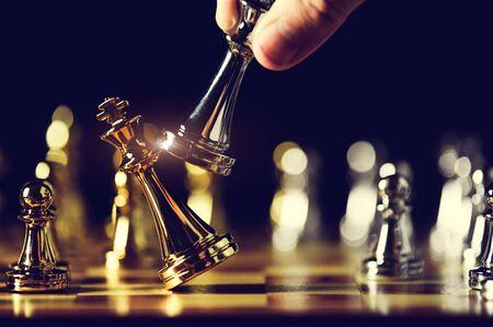La pièce d'échecs du roi en gros plan a vaincu l'ennemi ou le concurrent commercial par échec et mat à la fin du jeu d'échecs. Homme d'affaires déplaçant les échecs à la compétition à la main. Direction et gestion de la stratégie