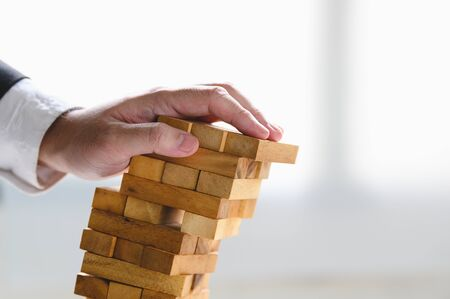 Businessman collapsing stacked tower wood block by hand as failure or bankrupt project. Business organization and company unsuccessful progress. Strategy and money investment. Risk management