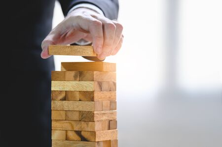 Businessman arranging wood block and stacking as tower by hand. Business organization and company growth progress. Success of strategy and money investment concept. Risk management project theme