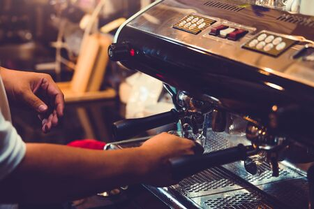 Closeup of professional male barista hand making cup of coffee with coffee maker machine in restaurant or coffee shop. People and lifestyles. Business food and drink concept. Shop owner theme Banco de Imagens