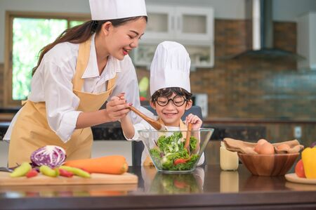 Happy beautiful Asian woman and cute little boy with eyeglasses prepare to cooking in kitchen at home. People lifestyles and Family. Homemade food and ingredients concept. Two Thai people life
