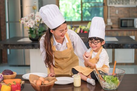 Happy beautiful Asian woman and cute little boy with eyeglasses prepare to cooking in kitchen at home funny. People lifestyles and Family. Homemade food and ingredients concept. Two Thai people life Stock Photo