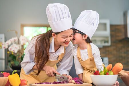 Happy cute little boy with eyeglasses kissing beautiful Asian woman mother while prepare to cooking in kitchen at home. People lifestyles and Family. Homemade food and ingredients concept.