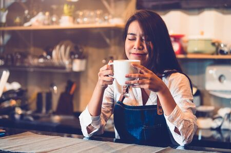 Beauty Asian female barista holding cup of coffee and tasting brewed coffee  with cafe restaurant background. Waitress smelling coffee at cafeteria. Food and drink concept. People lifestyle