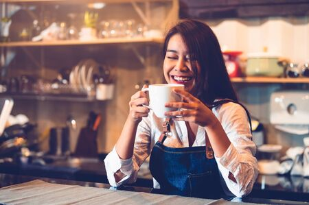 Happy Asian female barista holding cup of coffee and tasting brewed coffee from herself with cafe restaurant background. Waitress at cafeteria. Food and drink. People lifestyle and occupation concept. Stock Photo
