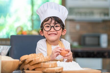 Portrait cute little Asian happy boy interested in cooking funny in home kitchen. People lifestyles and Family. Homemade food and ingredients concept. Baking Christmas cake and cookies. Smiling child