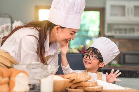 Cute little Asian boy painting beautiful woman face with dough flour. Chef team playing and baking bakery in home kitchen funny. Homemade food and bread. Education teamwork and learning concept.