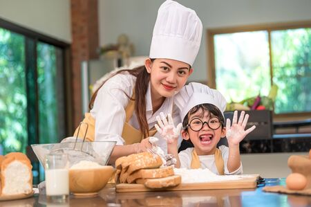 Beautiful woman and cute little Asian boy with eyeglasses, chef hat and apron playing and baking bakery in home kitchen funny concept. Homemade food and bread. Funny face emotion looking camera