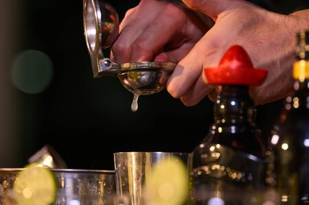 Closeup bartender hand preparing fresh juice cocktail in drinking wine glass with ice at night bar clubbing counter. Occupation and people lifestyles concept. Outdoor and nightclub background Banco de Imagens