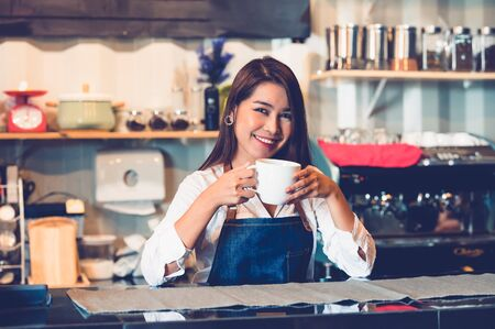 Asian female barista making cup of coffee. Young woman holding white coffee cup while standing behind cafe counter bar in restaurant background. People lifestyles and Business occupation concept.