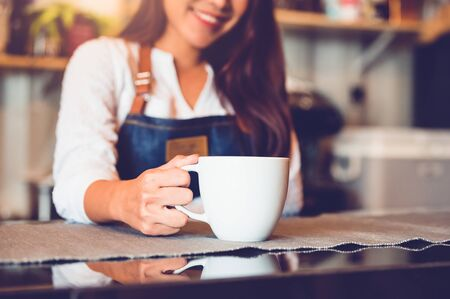 Closeup of white coffee cup with beautiful Asian woman barista background for serving to customer. Job and occupation. Food and drink beverage. Coffee shop and Cafe. Business and restaurant ownership Stock Photo