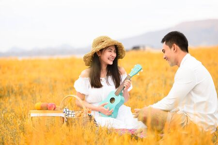 Two Asian young couples in autumn meadow field doing picnic in honeymoon trip in white clothes, ukulele guitar and fruits basket. People lifestyle and wedding concept. Nature and travel day concept.