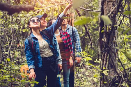 Group of Asian friendship adventure in forest jungle view background. Girl pointing finger to sky or tree top. People lifestyle travel on vacation concept. Summer picnic and camping. Trekking hiking