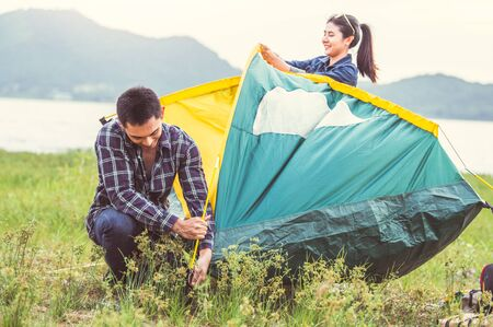 Two Asian couples prepare pitch camping tent to stay outdoors meadow overnight for honeymoon camping picnic. People lifestyle and Valentine day love concept. Nature travel vacation relaxation activity Zdjęcie Seryjne