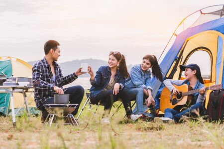 Groupe d'amis asiatiques trinquant à une bouteille à boire pour célébrer en soirée privée avec arrière-plan vue sur la montagne et le lac. Le mode de vie des gens voyage sur le concept de vacances. Tente de pique-nique et de camping