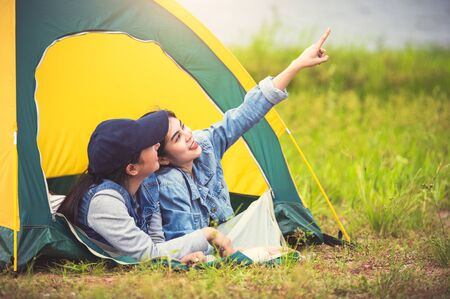 Two close friend Asian friendship relax in camping tent in green meadow on lake side view background. Girl pointing finger to sky. People lifestyle travel on vacation concept. Summer picnic activity Stock Photo
