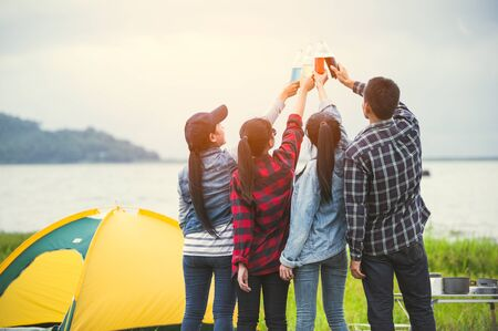 Back view of friendship clinking drinking bottle glass for celebrating in private party with mountain and lake view background. People lifestyle and travel on vacation concept. Picnic and camping tent