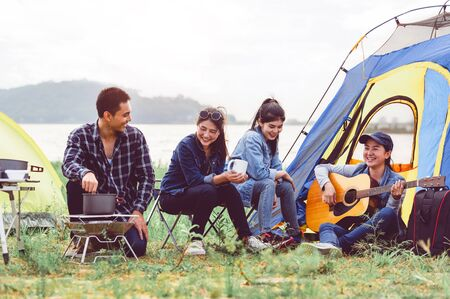 Group of Asian friendship clinking drinking bottle glass for celebrating in private party with mountain and lake view background. People lifestyle travel on vacation concept. Picnic and camping tent Stock Photo