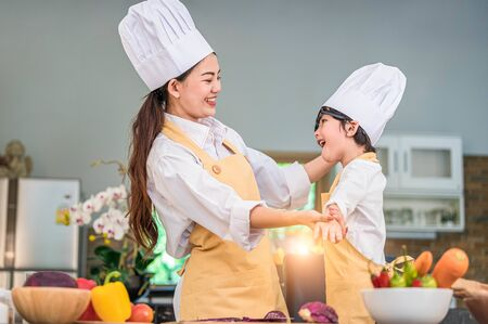 Happy beautiful Asian woman dress up cute little boy chef outfit for prepare to cooking in home kitchen. People lifestyles and Family. Homemade food and ingredients concept. Two Thai people life Stock Photo