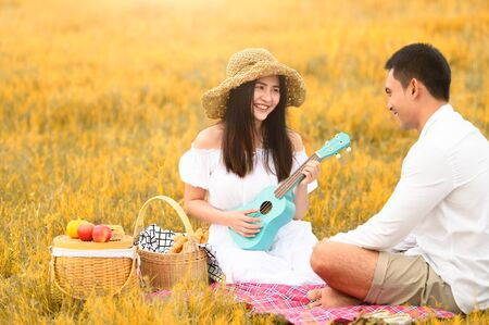Two Asian young couples in autumn meadow field doing picnic in honeymoon trip in white clothes, ukulele guitar and fruits basket. People lifestyle and wedding concept. Nature and travel day concept. Foto de archivo - 130157957