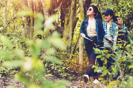 Group of Asian friendship adventure in forest jungle view background. Girl leading tourism team in nature. People lifestyle travel on vacation concept. Summer picnic and camping. Trekking hiking