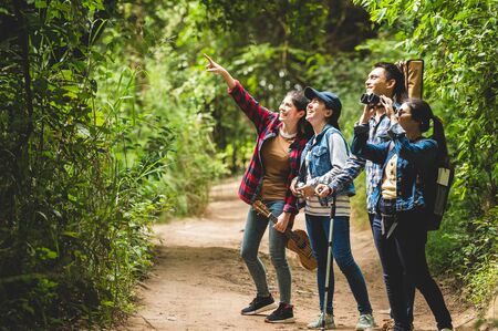Group of Asian friends team adventure for hiking and camping in forest together. Family travel relaxation. Trekking and trail activity in wild life concept. Woman pointing at tree or sky. Copy space Stock Photo