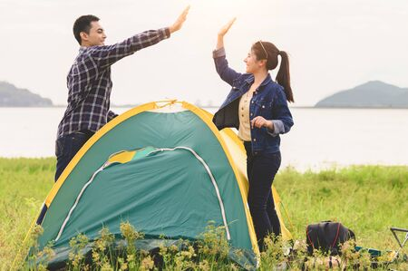 Two Asian couples finished pitch and doing high five for stay in camping tent  meadow overnight honeymoon picnic. People lifestyle and Valentine day love concept. Nature travel relaxation activity Zdjęcie Seryjne - 130158090