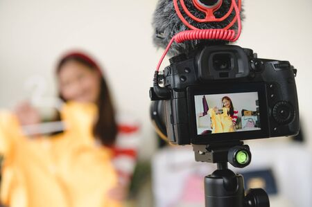 Professional DSLR digital camera film video live with vlogger blogger interview background. Woman coaching trading and review clothing product. Business presentation training class. People lifestyle