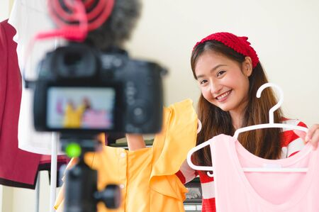 Beauty Asian Vlogger blogger interview with professional DSLR digital camera film video live. Woman coaching trading and review clothing product. Business presentation training class. People lifestyle