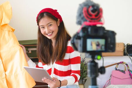 Beauty Asian Vlogger blogger interview with professional DSLR digital camera film video live and tablet. Woman coaching trading and review clothing product. Business presentation training class.