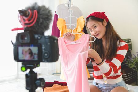 Beauty young Asian Vlogger blogger interview with professional DSLR digital camera film video live. Woman coach trading review clothing product. Business presentation training class. People lifestyle