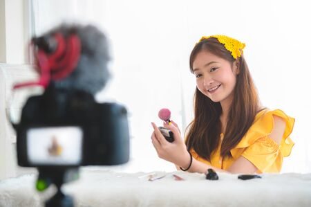 Happy Asian young beauty blogger girl training how to be make up artist in home studio. Woman speaking in front of camera as vlogger. Female vlog blogger recording video tutorial upload to Internet Stock Photo