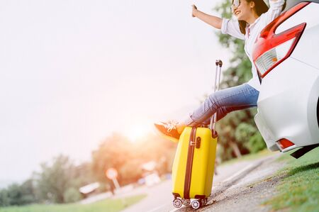 Happy Asian woman spread arms widely and breathed fresh air with happiness mood in on raod trip in car trunk. People lifestyle in long vacation trip concept. Outdoors nature and transportation Stock Photo
