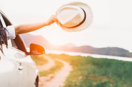 Happy woman hand holding hat outside open window car with meadow and mountain lake background. People lifestyle relaxing as traveler on road trip in holiday vacation. Transportation and travel concept Zdjęcie Seryjne - 130157668