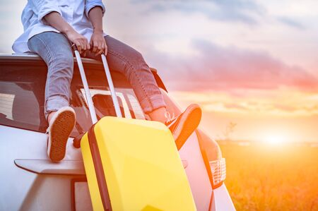 Closeup of happy Asian woman on top of car with luggage bag. Girl sitting on roof and looking sunset before evening. People lifestyle in long vacation trip concept. Nature and transportation vehicle