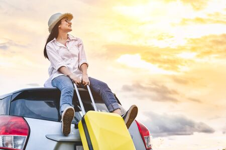 Happy Asian woman on top of car with luggage bag. Girl sitting on roof and looking sunset before night in evening. People lifestyle in long vacation trip concept. Nature and transportation vehicle.