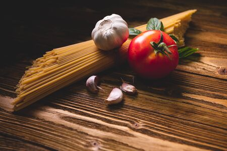 Tasty appetizing italian spaghetti pasta ingredients for kitchen cuisine with tomato, garlic and basil on wooden brown table. Food meal and Italian recipe homemade. Top view abgle above Banco de Imagens
