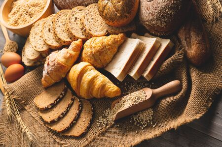 Different kinds of bread with nutrition whole grains on wooden background. Food and bakery in kitchen concept. Delicious breakfast gouemet and meal. Top view angle