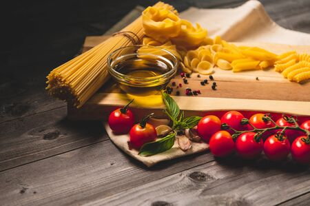 Tasty appetizing italian spaghetti pasta ingredients for kitchen cuisine with tomato, cheese parmesan, olive oil, fettuccine and basil on wooden brown table. Food Italian recipe homemade. Top view