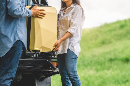 Asian man helping woman to lifting suitcase from car during travel in long weekend. Couple have road trip in vacation with yellow luggage. People lifestyle and transportation concept. Nice guy theme Stok Fotoğraf
