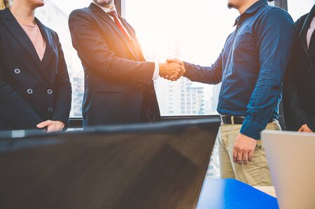 Business partnership meeting handshaking concept. Businessmen doing handshake. Successful business people contract handshaking after finished good dealing with skyscraper window building background. Standard-Bild