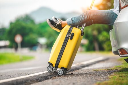 Closeup of yellow luggage and woman legs relaxing on back of car with road background. Road trip and holiday vacation concept. People lifestyles and transportation. Girl spending weekend in roadtrip
