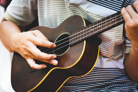 Closeup of guitarist hand playing guitar. Musical instrument concept. Outdoors and Leisure theme. Selective focus on left hand. Vintage country folk guitar with music singer. Close up entertainer hand Banque d'images - 138737354